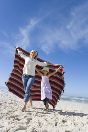 Mother and daughter (5-7) holding up blanket on beach, smiling, low angle view LANG_EVOIMAGES