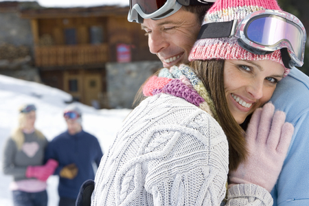 Young couple embracing in snow field, smiling, friends smiling in background LANG_EVOIMAGES