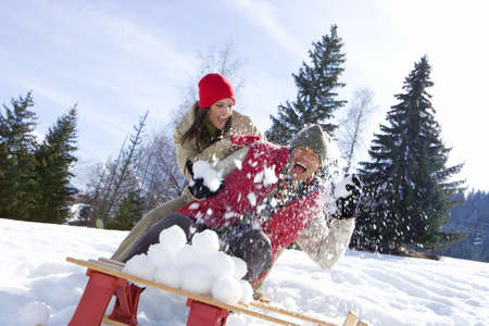 Young couple having snow fight in snow field, sled in foreground