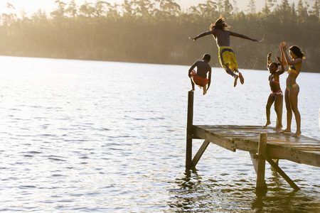 Father and son (8-10), in swimwear, jumping off jetty into lake at sunset, mother and daughter (7-9) cheering, rear view
