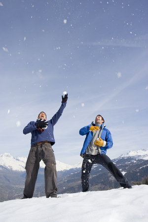 Two young men catching snow falling from sky, laughing, mountain range in background LANG_EVOIMAGES