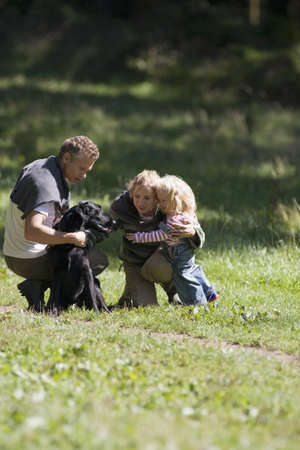 Two generation family walking dog in field, parents crouching beside girl (2-3) on grass