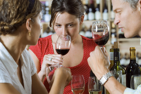 Friends wine tasting in off-licence, woman smelling glass of red wine (differential focus)