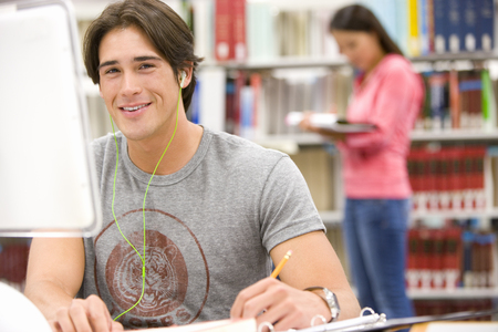 Young man with earphones sutdying in library, smiling, young woman in background