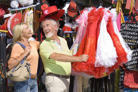 Senior couple shopping, man in hat showing dress to wife, smiling