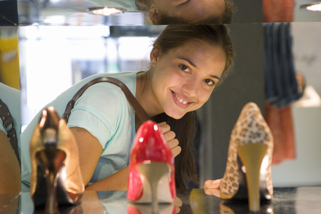 Teenage girl (16-18) standing by high heels on shelf, smiling, portrait