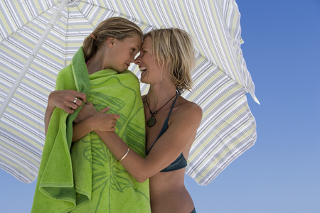 Mother embracing daughter (9-11) wrapped in green beach towel beneath sunshade, rubbing noses
