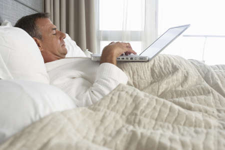 Businessman in bathrobe lying in hotel bed, using laptop, profile LANG_EVOIMAGES