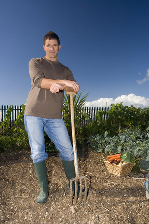 Man in garden with pitchfork, portrait, low angle view