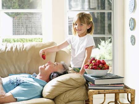 Senior woman lying on sofa at home, granddaughter (6-8) feeding her strawberries, side view, portrait LANG_EVOIMAGES