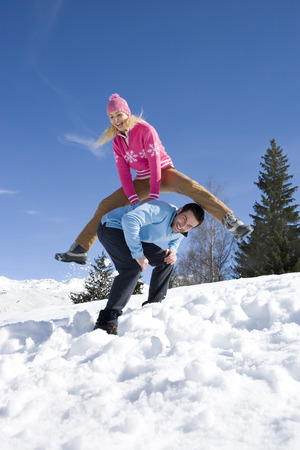 Young couple in snow field, smiling, portrait, woman jumping over man