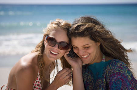 Two young women standing on beach, using mobile phone, smiling LANG_EVOIMAGES