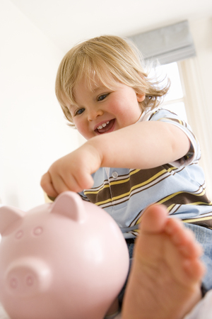 Baby boy (9-12 months) putting coin in piggy bank, smiling, low angle view (differential focus)