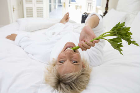 Woman wearing white bath robe, biting on celery, smiling, portrait LANG_EVOIMAGES