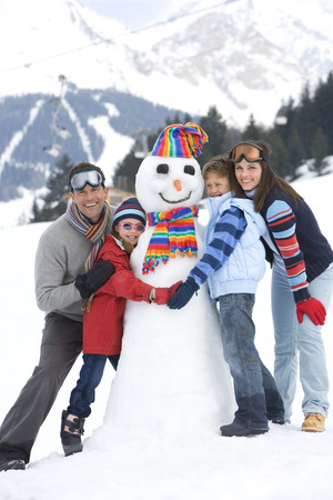 Family of four embracing snowman in snow, smiling, portrait