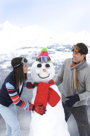 Couple smiling at each other by snowman in snow, smiling, mountain range in background LANG_EVOIMAGES