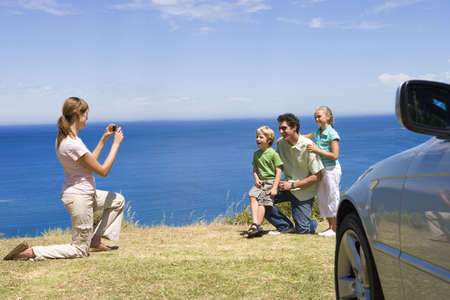 Woman photographing family on clifftop overlooking Atlantic Ocean, smiling, side view LANG_EVOIMAGES