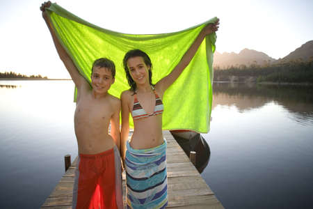 Teenage boy and girl (12-14) standing on lake jetty at sunset, holding aloft green towel, smiling, portrait LANG_EVOIMAGES