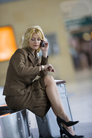 Businesswoman waiting for luggage in airport baggage claim area, checking time, using mobile phone