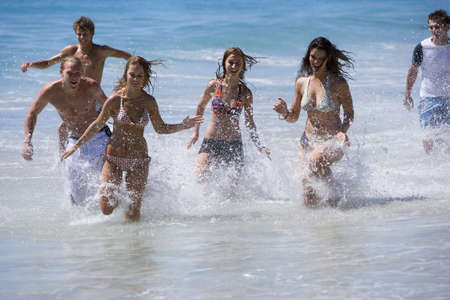 Group of teenagers (17-19) running in surf at beach, smiling, front view LANG_EVOIMAGES