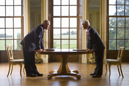 Businessman and colleague looking at each other over table, side view