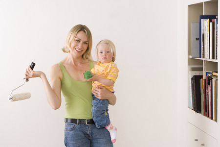 Woman holding paint roller and daughter (12-15 months) by bookshelf, smiling, portrait LANG_EVOIMAGES