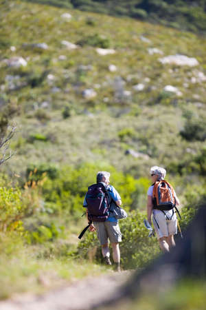 Mature couple hiking on mountain trail, carrying hiking poles and rucksacks, rear view