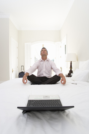 Mature businessman meditating on bed, laptop in foreground