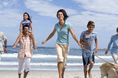 Multi-generational family walking dog on beach, girl (6-8) on fathers shoulders, smiling