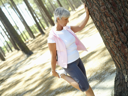 Active senior woman leaning against tree, stretching leg, side view (tilt) LANG_EVOIMAGES