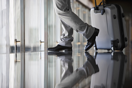 Businessman leaving lobby with luggage, side view, low section, surface level, reflection on floor LANG_EVOIMAGES