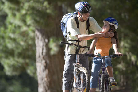 Father and daughter (7-9) mountain biking on woodland trail, man adjusting strap of girls cycling helmet
