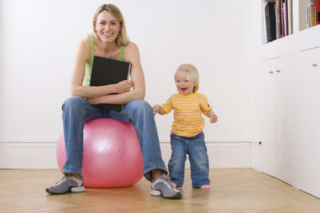 Woman with book on exercise ball by baby daughter (12-15 months,) smiling, portrait, low angle view LANG_EVOIMAGES