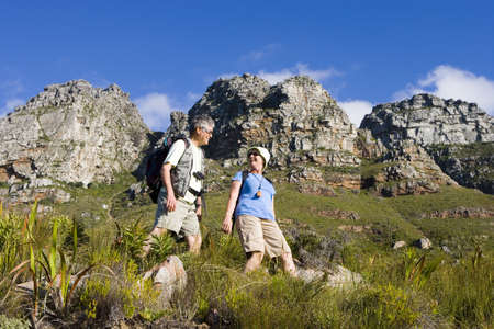 Mature couple hiking on mountain trail, carrying rucksacks, smiling, side view, low angle view LANG_EVOIMAGES