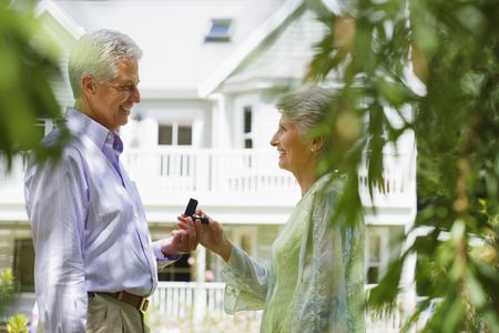 Senior man proposing to senior woman in summer garden near house, smiling, profile LANG_EVOIMAGES