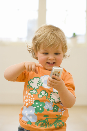 Male toddler (15-18 months) playing with mobile phone, smiling, close-up