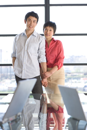 Young couple standing together by window, smiling, portrait, laptops on glass table in foreground