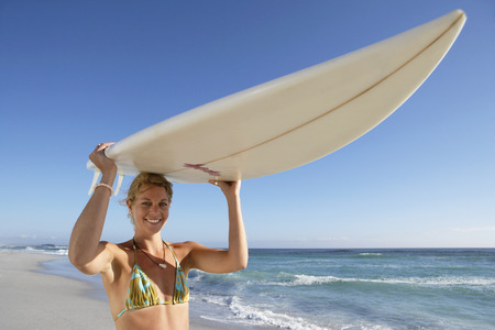 Young woman standing on beach, carrying surfboard on head, smiling, portrait, sea in background LANG_EVOIMAGES