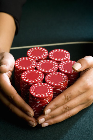 Woman with hands around piles of gambling chips on table, close-up LANG_EVOIMAGES