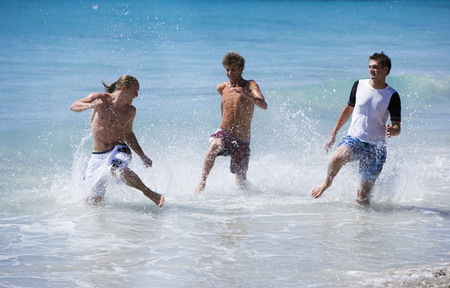 Three teenage boys (17-19) playing in surf at beach, smiling LANG_EVOIMAGES