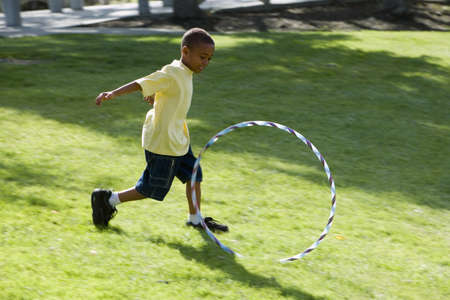Boy (6-8) chasing plastic hoop on grass in park, smiling, side view
