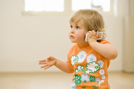 Toddler indoors talking on mobile phone