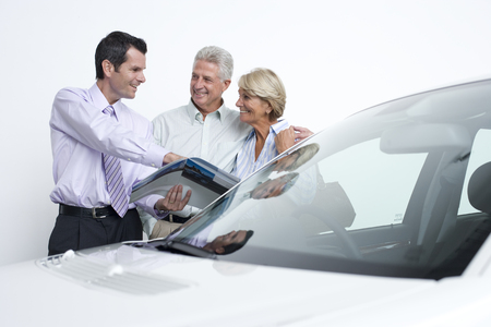 Car salesman talking to couple about new car LANG_EVOIMAGES