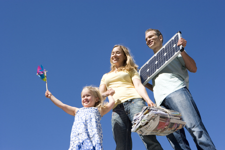 30s couple holding solar panel and newspapers for recycling with 5 year old daughter holding coloured windmill outdoors against blue sky