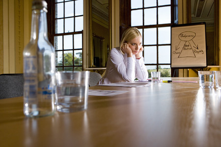 Businesswoman at table by whiteboard, head in hands, low angle view