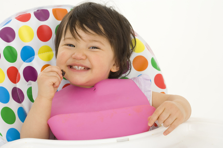 Baby girl (3-6 months) in highchair, smiling, portrait