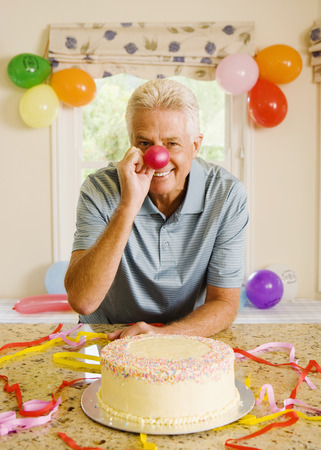Senior man sitting beside birthday cake at home, holding deflated red balloon over nose, smiling, front view, portrait
