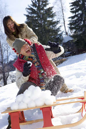 Young couple having snow fight, snow ball pile on sled in foreground LANG_EVOIMAGES