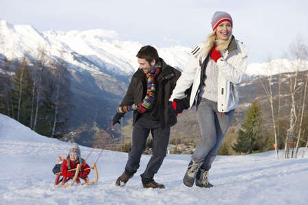 Young couple pulling daughter (7-9) on sled in snow field, smiling, mountain range in background