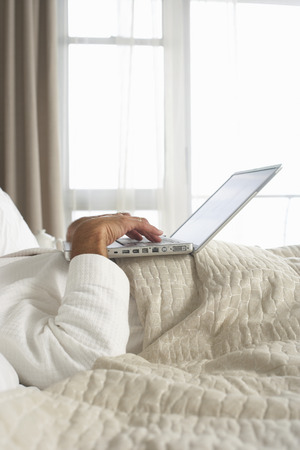 Businessman in bathrobe lying in hotel bed, using laptop, side view, mid-section LANG_EVOIMAGES